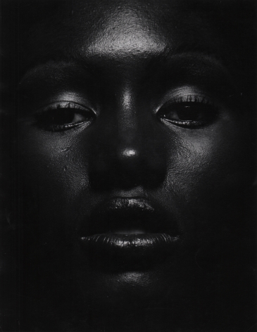 07. Anthony Barboza, Grace Jones, ​1970s. Close up of the model's dimly-lit face, eyes looking to the camera and lips slightly parted.