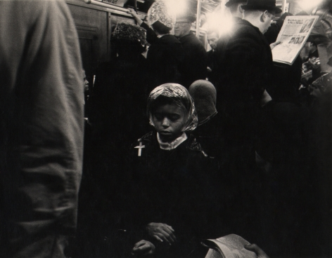 04. Beuford Smith, Palm Sunday, ​1968. A woman seated on a crowded subway, hands crossed in her lap and eyes closed.