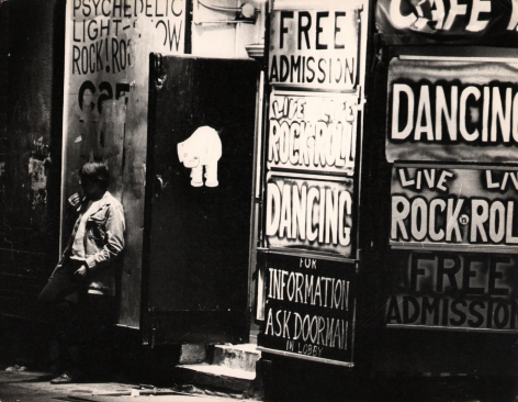 """10. LeRoy Henderson, Cafe Wha! Greenwich Village, N.Y. (MacDougal Street), c. 1965. Man leas against building covered in signs such as """"Free admission,"""" Live Rock n' Roll,"""" and """"Dancing"""""""