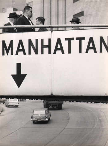 """09. Jan Lukas, Untitled, 1964. Pedestrians walk over a footbridge labeled """"Manhattan"""" above a multi-lane road with cars."""