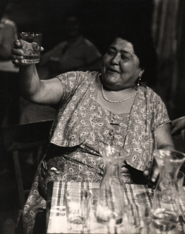 Carlo Bavagnoli, Gente di Trastevere, ​1957–1958. A smiling woman seated at a table raises her drinking glass in a toast.