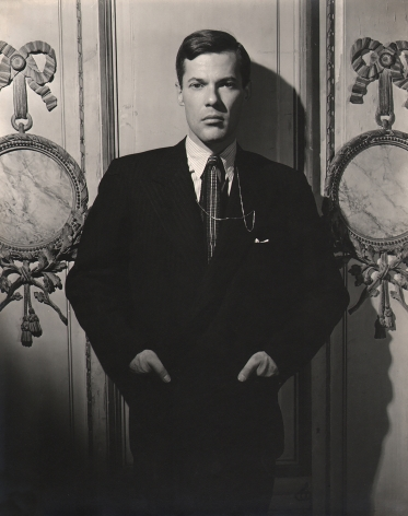 George Platt Lynes, Glenway Wescott, n.d. Subject stands in a suit, hands in pockets, against a lavish wall.