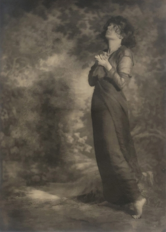 06. Mesdames Morter, Love Praying - Self-Portrait, 1923. A woman stands in a dimly lit room in a long draping, dress with one hand on her hip, looking down.