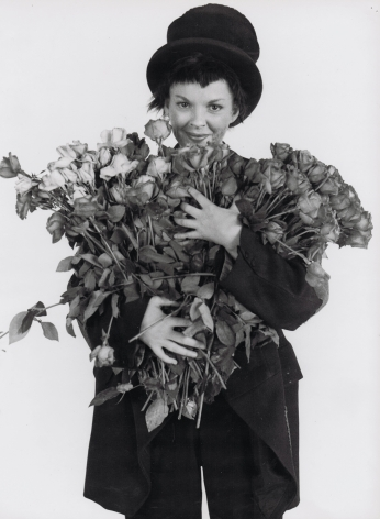 Richard Avedon, Judy Garland, 1951. A woman in a suit and top hat holds a large bouquet of flowers.