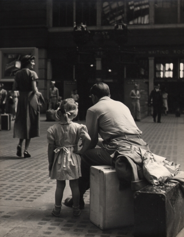 07. Simpson Kalisher, Untitled (Penn Station), c. 1949. Rear view of a young girl standing beside a man sitting on a suitcase.
