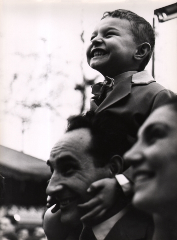 Mario Cattaneo, Untitled, c. 1960. A young boy sits on a man's shoulders, holding on to his face. A woman's face is out of focus in the foreground. All are smiling and looking to the left of the frame.