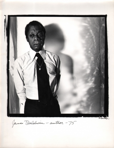 Anthony Barboza, James Baldwin, Author, 1975. Subject stands to the left side of a square frame, looking down and to the left. His shadow is cast to the right on the wall behind him.