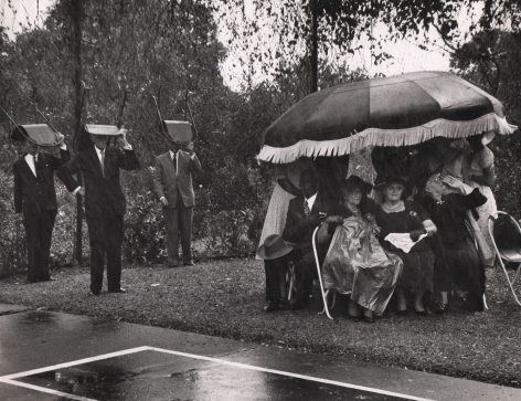 Leonard McCome, Governor's Garden Party, Grenada Island, ​c. 1959. Guests huddle under a large umbrella on the right of the frame while three suited men on the left hold chairs above their heads.