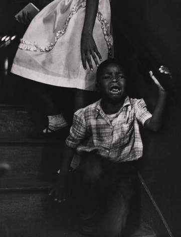 Marvin E. Newman, Chicago, ​1950. A young boy cries, facing away from the skirt of an adult female figure pictured from the waist down.