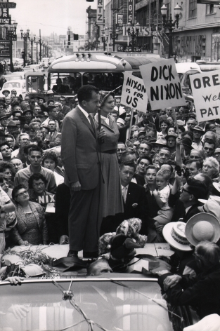 "Ed Clark, Nixon campaigning in the 1960 presidential election, ​1960. Subject stands on the back of a car speaking into a microphone surrounded by a large crowd holding signs such as ""Nixon is for us"" and ""Dick Nixon"""