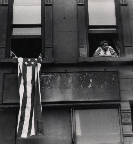 01. Beuford Smith, Flag Day, Harlem, 1976. Detail of two windows of an apartment building; a woman leans out of the right window, an American flag hangs from the left.
