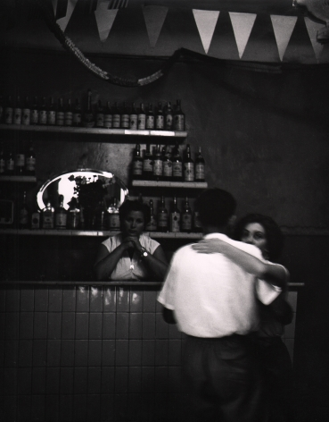 Piergiorgio Branzi, Firenze, Ballo alla casa del popolo di San Frediano, ​1959. A couple dances in the foreground with a woman looking on from behind the bar in the background.