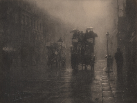 03. Léonard Misonne, Rue royale, 1936. Two horse-drawn carriages carrying figures with umbrellas on a wet street. Sepia-toned print.