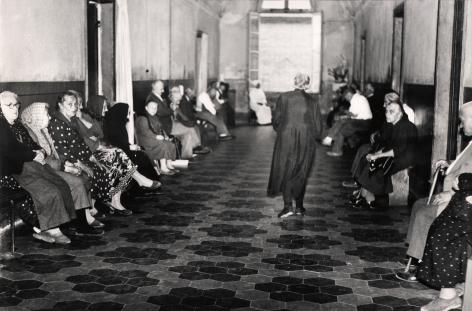 05. Mario Giacomelli, Verrà la morte e avrà i tuoi occhi, 1966–1968. High contrast image. A woman walks down a hallway, back to the photographer. The hall is lined with seated women.