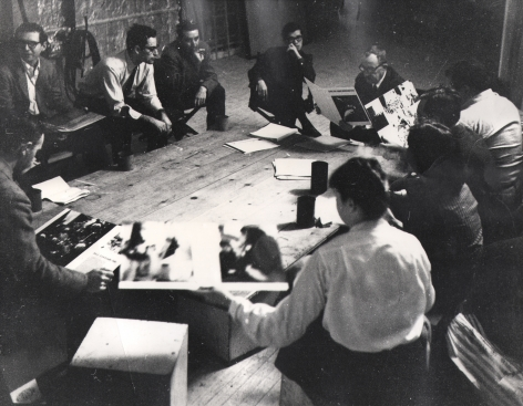 03. David Attie, Brodovitch Design Laboratory, Richard Avedon's Studio, c. 1957. A group of at least ten people sit in a circle on a wooden floor, reviewing prints.