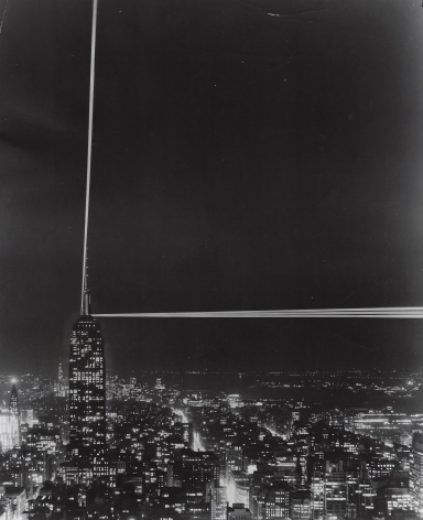 08. Anonymous, Patterns in Light: the Empire State's controversial beacons, 1956. Distant, head-on nighttime view of the Empire State Building (lower left of frame), with two beams of light streaming up and to the right.