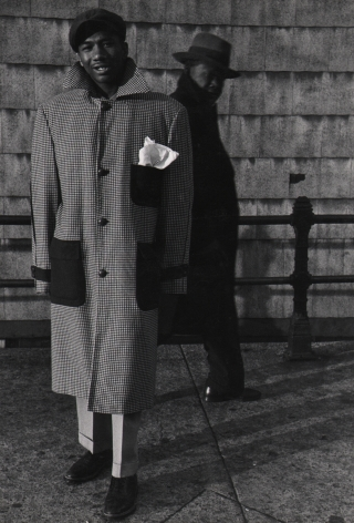 Marvin E. Newman, Chicago, ​1950. A young adult male in a large coat stands on the sidewalk, smiling to the camera, another man in black walks by in the background.