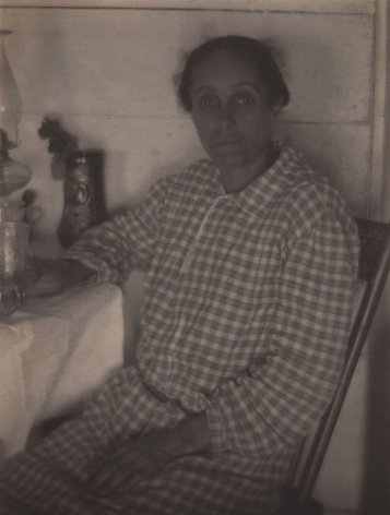 Doris Ulmann, Untitled (Appalachian woman), ​1928–1934. Woman in a checkered dress seated at a table and looking to the camera. One hand is in her lap, the other rests on the table by a drinking glass.