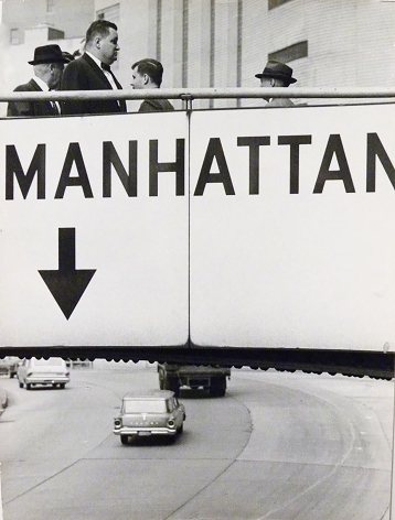 "4. Jan Lukas, Untitled, ​1964. Pedestrians walk over a footbridge labeled ""Manhattan"" above a multi-lane road with cars."