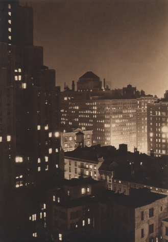 Paul J. Woolf, Untitled, c. 1933. Night time cityscape above and at the level of the right side buildings, with a taller building occupying the left of the frame.