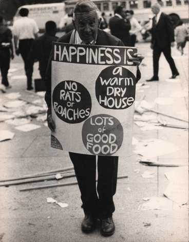 "9. LeRoy Henderson, Washington, D.C. Poor People's Campaign, ​1968. Older man stands in the street holding a sign that reads ""Happiness is: a warm dry house, no rats, or roaches, lots of good food"""
