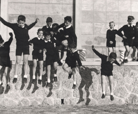 Nino Migliori, People of Emilia, 1957. A group of schoolboys jumping from a low wall.