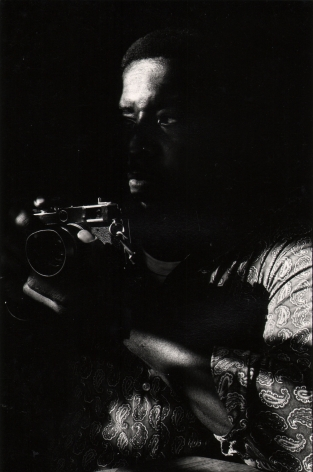 08. Anthony Barboza, Lou Draper, ​1970s. Dimly lit torso of a man facing left and holding a camera at chest-level.