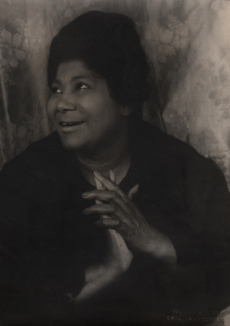 08. Carl Van Vechten, Mahalia Jackson, 1962. Bust-length portrait with subject smiling towards the upper left of the frame with hands clasped at her chest.