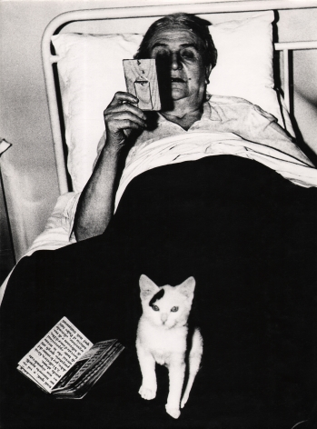 07. Mario Giacomelli, Verrà la morte e avrà i tuoi occhi, 1966–1968. High contrast image. A woman in bed with a book and kitten in her lap, looking at a small frame in her right hand..