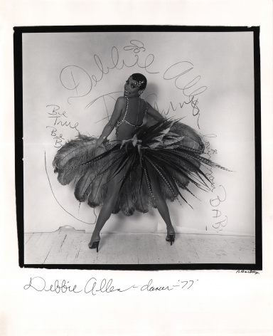 Anthony Barboza, Debbie Allen - Dancer, 1977. Subject stands in feathered skirt, back to camera, legs wide. Head is turned smiling to camera. Writing on white backdrop includes her name.