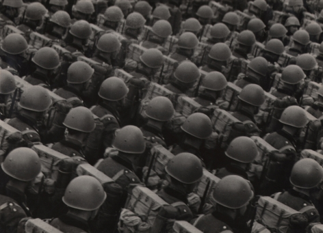 Italo Bertoglio, Le case di fronte, c. 1937. Diagonally composed rows of soldiers in helmets photographed from behind.