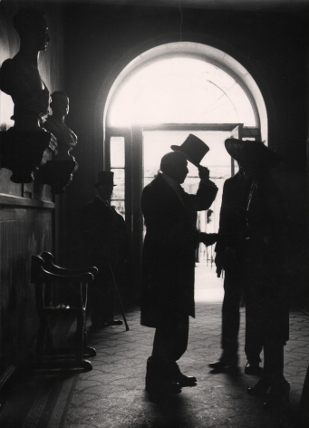 13. Lord Snowdon, The late Mr. William Stone, in Albany, London, c. 1966. Figures silhouetted in front of a doorway. Figure on the left lifts a tophat to two individuals facing him.