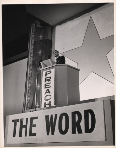 """Gordon Coster, Preach the Word, c. 1940. A suited man stands at a raised podium that reads """"Preach The Word"""". A large star is painted on the wall behind him."""