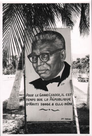"""08. Graham Finlayson, Haiti - Crude posters like this one - all of them extolling Duvalier for near-divine virtues, are emblazoned all along the main seafront road in Port au Prince, c. 1958–1966. A poster with a portrait of a man and the words """"pour le grand leader, il est temps que la République d'Haiti songe a elle-même"""""""