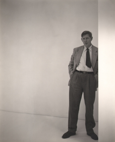 George Platt Lynes, W.H. Auden, 1947. Subject stands on the right of the frame leaning against a white wall.