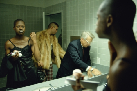 Three people in restroom by Lyle Ashton Harris