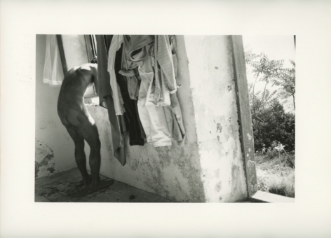 A black and white photograph of a naked man, leaning out of a window. At right we see an open doorway leading outside, there are clothes hung on the wall between the doorway and the man.