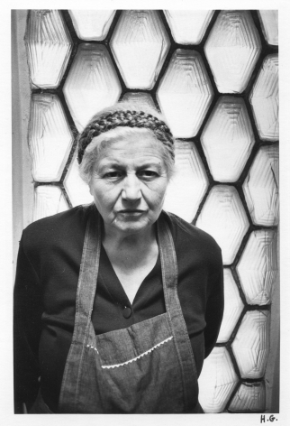 A black and white photograph of Guibert's great aunt, who is wearing a dark apron over a black blouse. In the background are glass hexagons.