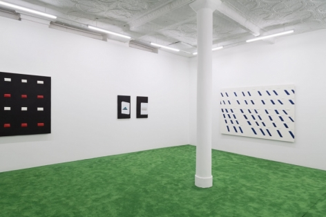 A photograph of the back quadrant of the gallery. There is an excerpt of a black, red, and white artwork at left; there are two smaller works to the left that depict cigarette cartons abstracted; and on the back wall at-right is a work with white and blue shapes.