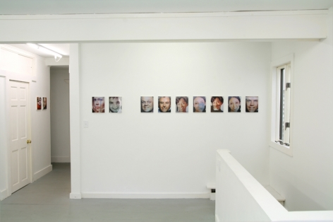 A photograph of 9 images on the central wall, and 2 in a hallway at left