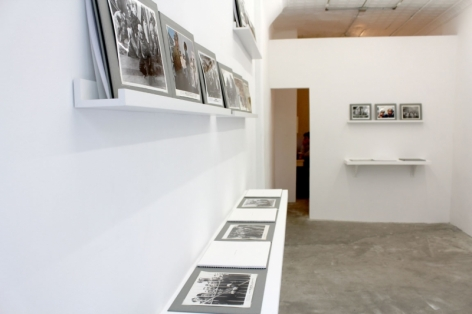A photograph of the gallery interior with 2 shelves at left with photographs upon them, and 2 shelves on the back wall