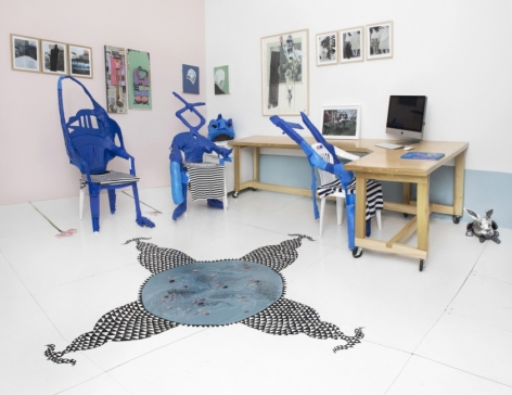 A photograph of the back office of the gallery that shows the desks and unique chairs created by the artists out of blue duct tape. On the walls are numerous mixed media works in natural frames. On the ground is the site-specific installation with black and white triangles.