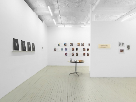 A photograph of the gallery with 4 black prints on the left wall on a shelf, leaning; a table with items on it in the middle-ground; a group of 4 items unframed on the temporary wall at right; and an excerpt of an artwork containing magazine spreads on the back wall.