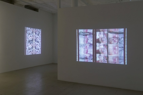 A photograph of two Luther Price video projections. In the foreground on the temporary wall we see images of an abstracted body parts; on the far wall to the left we see a body on the operating table.