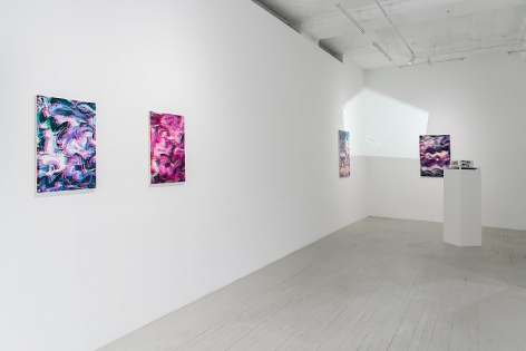 A view of 2 artworks installed on the wall directly at-left, with a view in the distance of 2 works installed around the far corner in the gallery. We see the projector and video being projected on these latter two works.