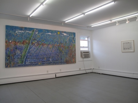 A photograph of gallery with a large horizontal blue painting on the wall at left, an abstract work on the wall at right