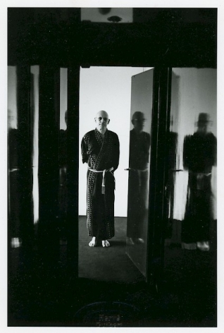 A black and white portrait of Michel Foucault in a robe, standing in a doorway. There is light in the hallway, his hands are behind his back.