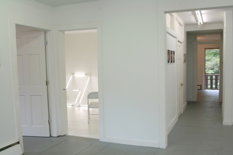 A photograph of a view down the hallway at right, and into the white room with G-L at left. There is an open door further to the left we cannot view inside