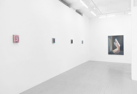 A photograph of 4 small paintings on the wall at left, detail indiscernible, and one large painting on the back wall of a kneeling naked woman seemingly made out of cellophane, looking at a wall.