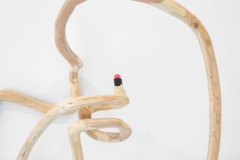 A plywood sculpture that is meant to look like a single carved line. This image is a close up of the wood clutching a tube of red lipstick.